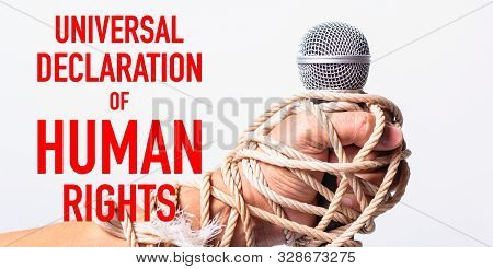 Hand Holding Microphone And Have Roped On Fist Hand With Universal Declaration Of Human Rights Text