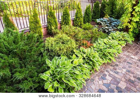 Landscaping In Home Garden. Beautiful Natural Landscape Design With Flower Beds In Summer. Scenic Vi