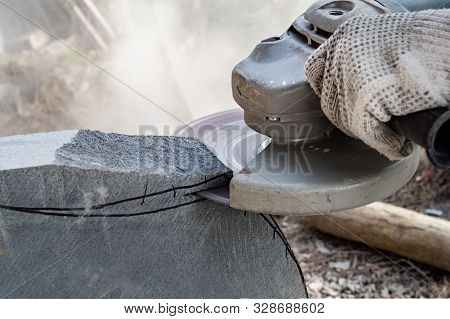 Man's Hands Holding Angle Grinder And Cutting  A Stone
