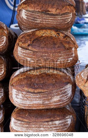 Freshly baked rustic sourdough bread on a food market stall poster
