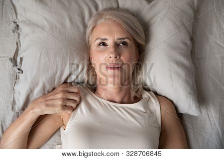 Middle Aged Woman Insomniac Lying Awake In Bed, Top View