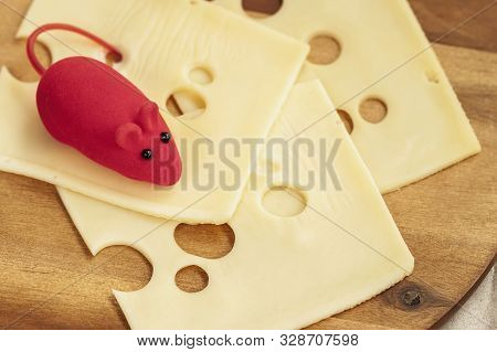 Mouse Toy On Flat Slices Of Natural Cheese With Holes. Close-up.