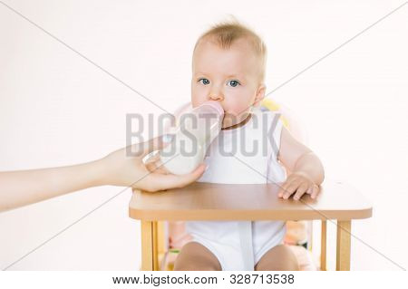 Mamas hand feeds the baby out of the bottle. The child is seated in a chair on a white background poster
