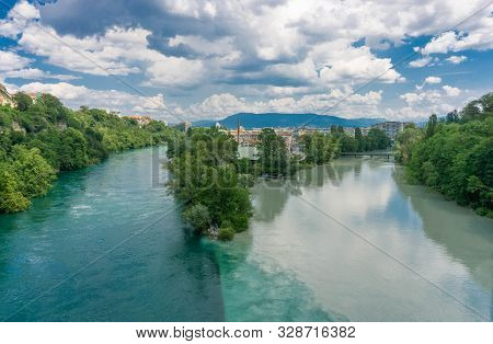Dark And Light River Merge Into A Single One. View From Above. White Shallow Clouds On A Blue Sky. T