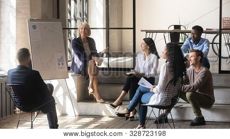 Happy Older Female Mentor And Diverse Business Team Discussing Presentation