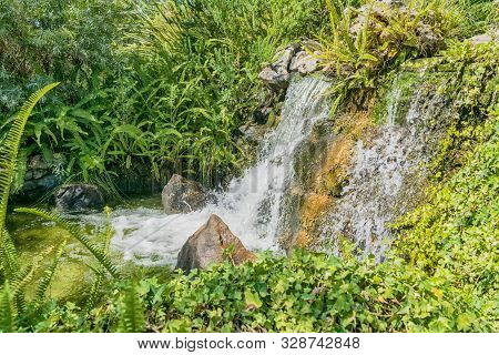 Waterfalls In Natural Landscape With Varied Vegetation.