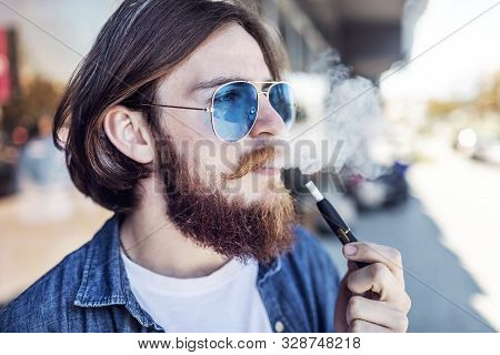 Youngster with brown hair and beard emitting smoke while smoking e-cigarette outdoors poster