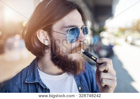 Casual Bearded Youngster In Mirrored Glasses Smoking Electronic Cigarette Outdoors