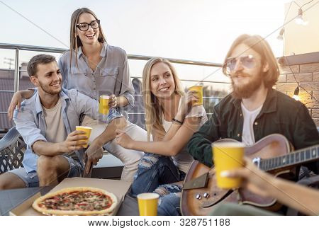Partying Youngsters Watch Their Bearded Brown-haired Friend Playing Guitar On A Sunny Terrace