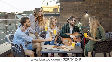True friends having beer and pizza and listen their pal playing the guitar on a sunset loft terrace poster