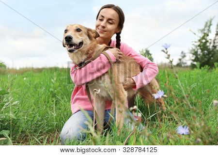 Female Volunteer With Homeless Dog At Animal Shelter Outdoors