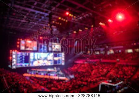 Blurred Background Of An Esports Event - Main Stage Venue, Big Screen And Lights Before The Start Of