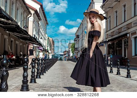 High Fashion Portrait Of A Graceful Woman In An Elegant Straw Hat And Dress That Walks Along A City