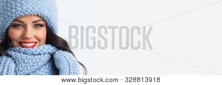 Smiling woman wearing blue winter hat, scarf and mittens studio isolated on white background