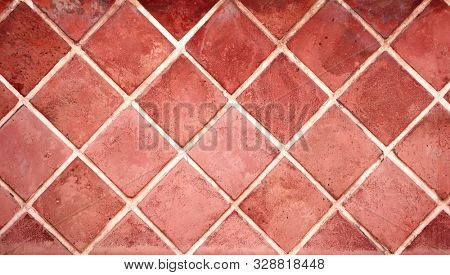 Old porcelain tiles floor texture with tiles of red color and cement of white color