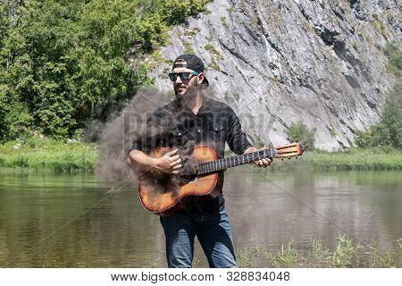 Crazy Man Musician, Guitarist On Vacation. 23 Year Guy With A Beard In A Black Shirt, Cap And Sungla