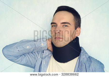 Man With Neck Brace After Whiplash Injury Blue Background, Black Neck Collar On Male Patient. Treatm