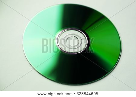 A Dvd Disc That Looks Green In The Sunlight From Windows Is On White Background