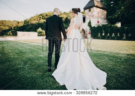 Gorgeous Bride And Groom Walking In Sunset Light. Beautiful Stylish Wedding Couple Embracing In Summ