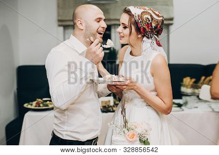 Bride And Groom Tasting Stylish Wedding Cake At Wedding Reception In Restaurant. Wedding Couple Plat