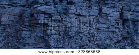Rock Cliff Face Background. Toned. Copy Space For User Text. Dangerous Vertical Wall With Protruding