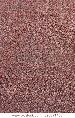 Surface of rubber pellets in treadmill athletics field texture background. Braun shock absorbing coatings are made from rubber chips that are used in playgrounds, stadiums and sidewalks poster