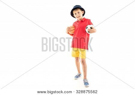 A Little Boy In Panama, Yellow Jersey, Red Shorts And White Sneakers Stands With Basketball And Socc