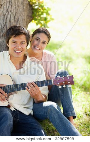 Woman smiling while resting her hand on the shoulder of her friend who i holding a guitar as they both sit against a tree