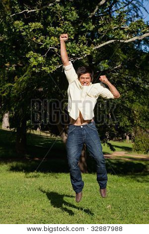 Man jumping off the ground while raising his arms while he is rejoicing in the park