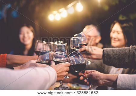 Happy Family Cheering With Red Wine At Reunion Dinner In Garden - Senior Having Fun Toasting Winegla