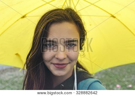 Portrait Of A Smiling Young Woman With Yellow Umbrella
