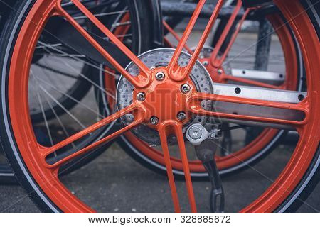 Close Up A Orange Rim Of A Bicycle For Rent