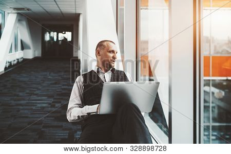 A Confident Serious Prosperous Caucasian Man Entrepreneur Is Sitting With A Laptop On A White Bench