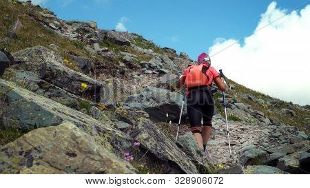 Woman Skyrunner Hiking In The Mountains With Nordic Walking Poles And Backpacker.