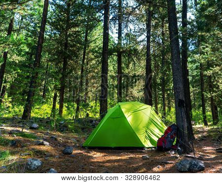 Tourist Camp In The Woods, Green Tent, Backpack And Poles. A Complete Set Of Equipment For A Good Hi
