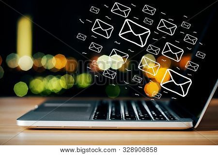 Side View Of Laptop On Desktop With Digital Emails On Bokeh Background. E-mail Network And Marketing