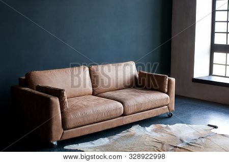 Luxurious Living Room Interior. Brown Leather Sofa In A Dark Room By The Window. Carpet Made Of Genu