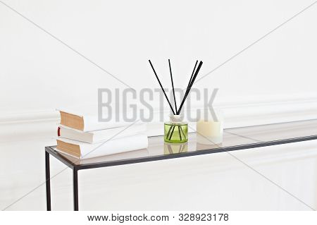 Reed Diffuser On Table In Room On A White Wall. Handmade Reed Freshener With A Candle On Commode In