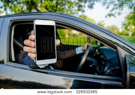 Young Businessman Lifted Their Smartphone In The Car.