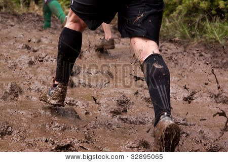POCONO MANOR, PA - APR 28: Participants run through large areas of deep mud at Tough Mudder on April 28, 2012 in Pocono Manor, Pennsylvania. The course is designed by British Royal troops.