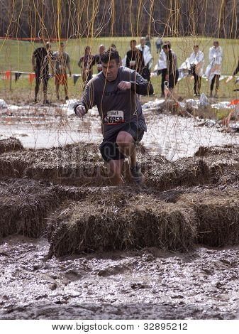 POCONO MANOR, PA - APR 28: A man runs through an obstacle with electrified wires at Tough Mudder on April 28, 2012 in Pocono Manor, Pennsylvania. The course is designed by British Royal troops.