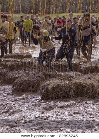 POCONO MANOR, PA - APR 28: Participants run through an obstacle with electrified wires at Tough Mudder on April 28, 2012 in Pocono Manor, Pennsylvania. The course is designed by British Royal troops.