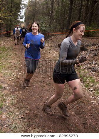 POCONO MANOR, PA - APR 28: Two women run on a trail through the woods at Tough Mudder on April 28, 2012 in Pocono Manor, Pennsylvania. The course is designed by British Royal troops.