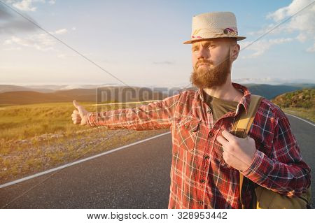 Stylish Barefoot Bearded Male Hitchhiker Traveler In A Hat And With A Backpack Walks Along A Suburba