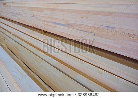 poster of Side view of stack of two-layer wooden glued laminated timber beams from pine finger joint spliced boards for wooden windows