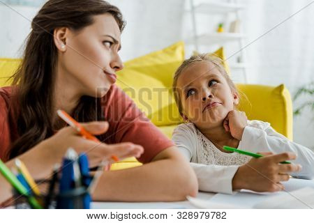 Selective Focus Of Babysitter Showing Shrug Gesture While Looking At Kid