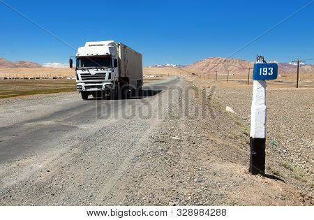 Pamir Highway Or Pamirskij Trakt And White Truck. Landscape Around Pamir Highway M41 International R