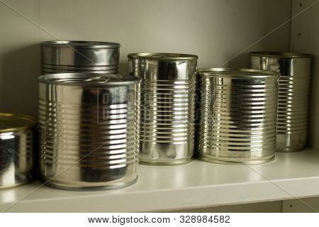Aluminum tin cans stocked in a food cupboard shelf poster