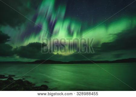 Northern Lights, Aurora Borealis In Kola Peninsula At Night Sky Illuminated Green. Murmansk Region,