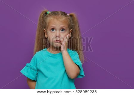 Sad Little Child Girl Suffering From Toothache Isolated On Purple Background. Upset Child With Tooth
